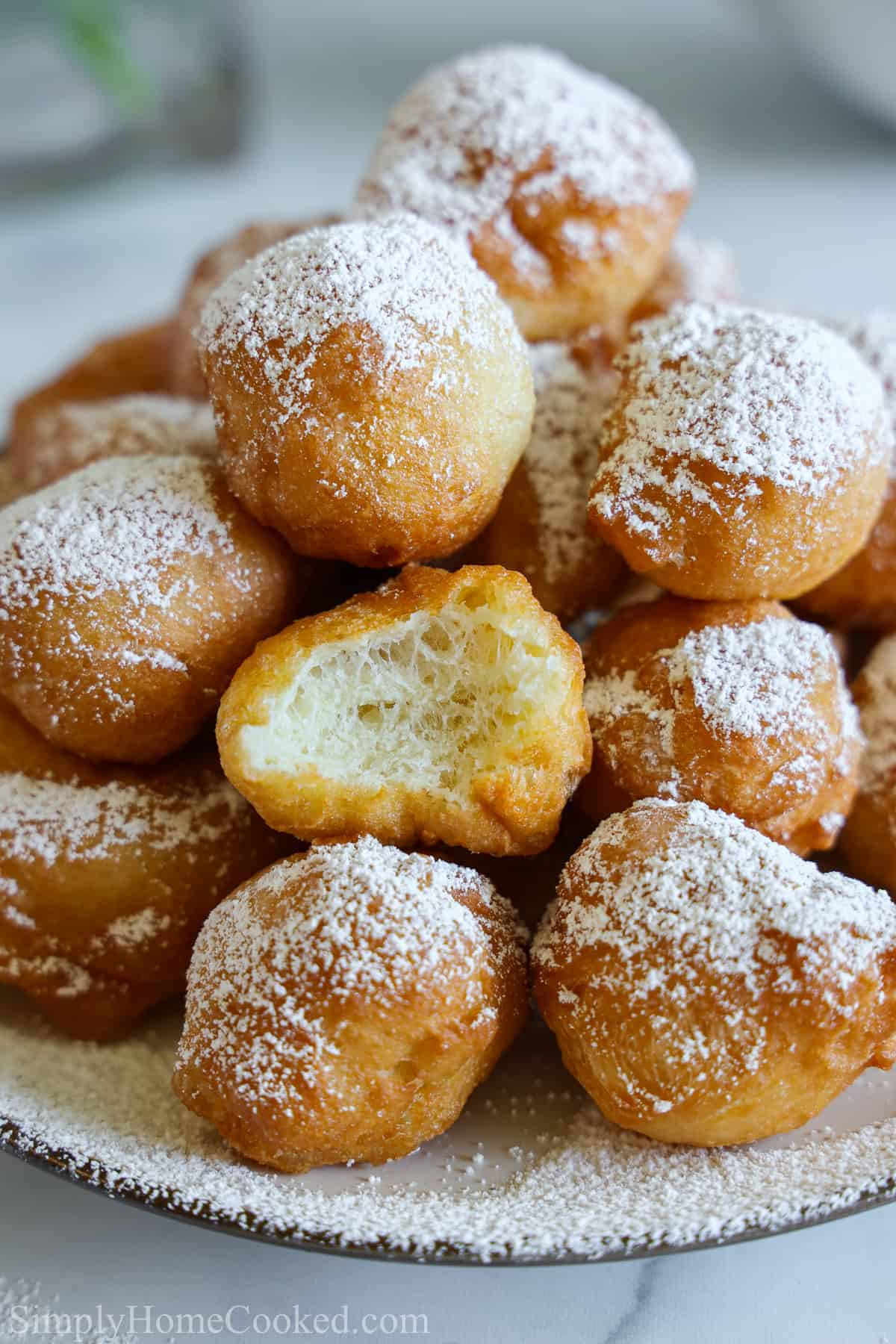 Close up of a pile of Zeppoles dusted with powdered sugar.