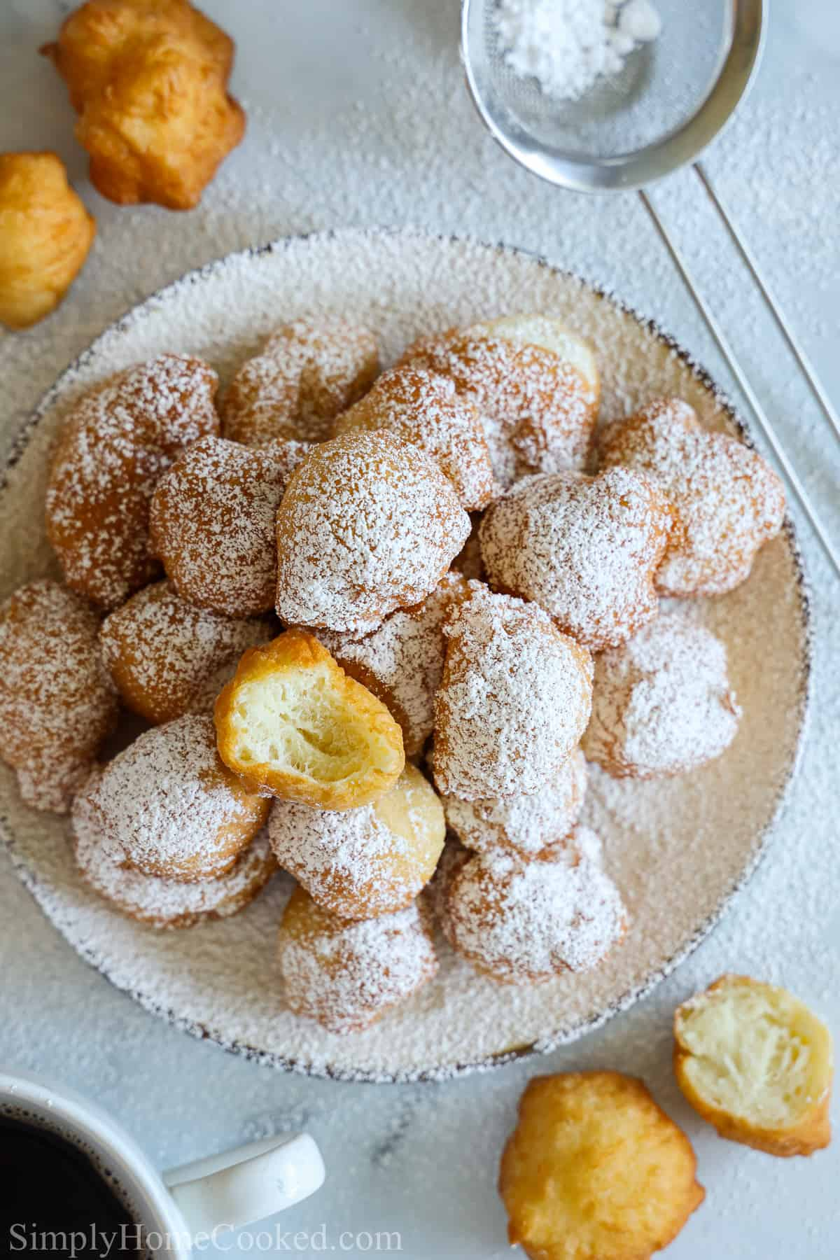 Plate of powdered sugar dusted zeppoles with one bitten, and some zeppoles and a small sieve to the side on a white background.