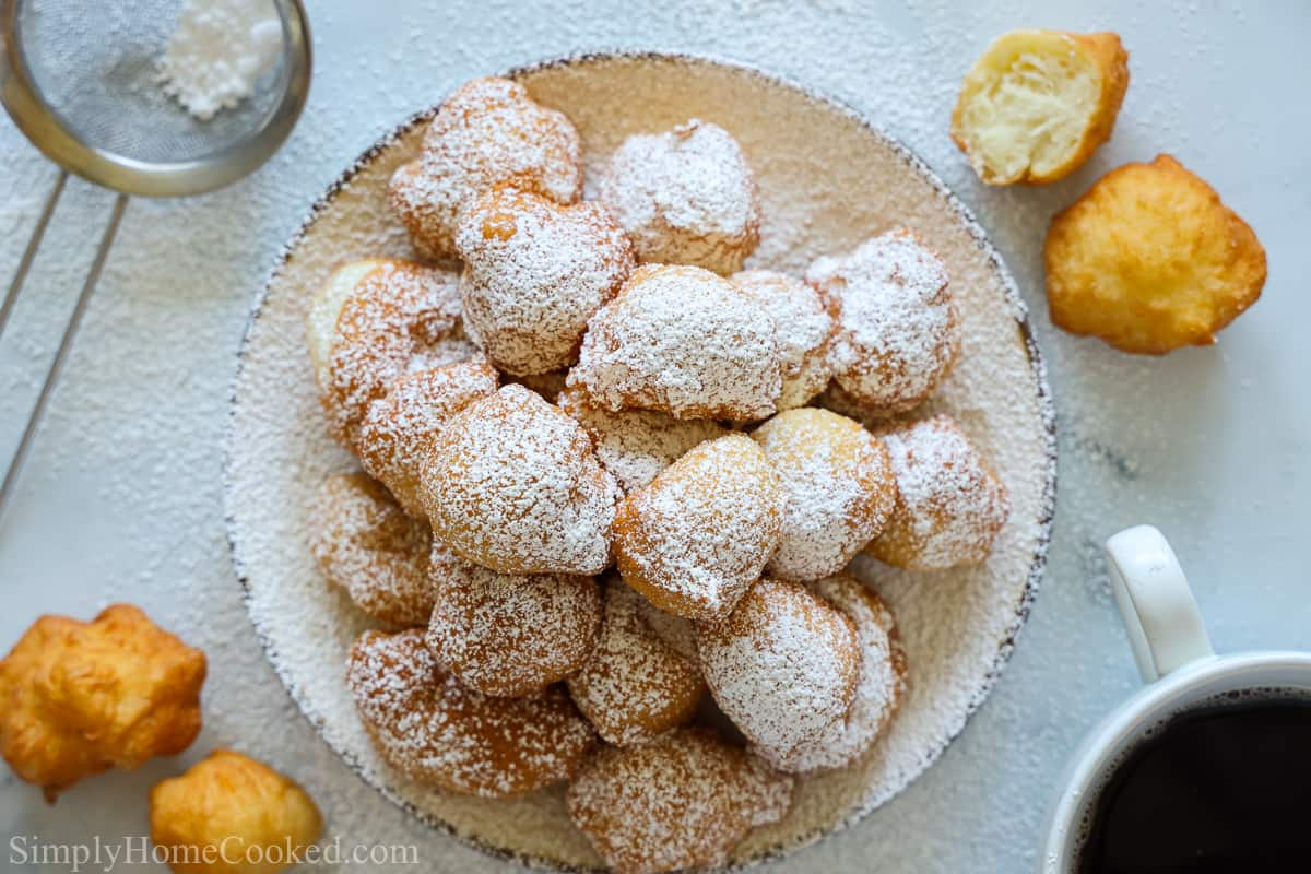 Overhead view of a plate of powdered sugar covered Zeppoles with some other zeppoles to the side with a sieve and cup of coffee.