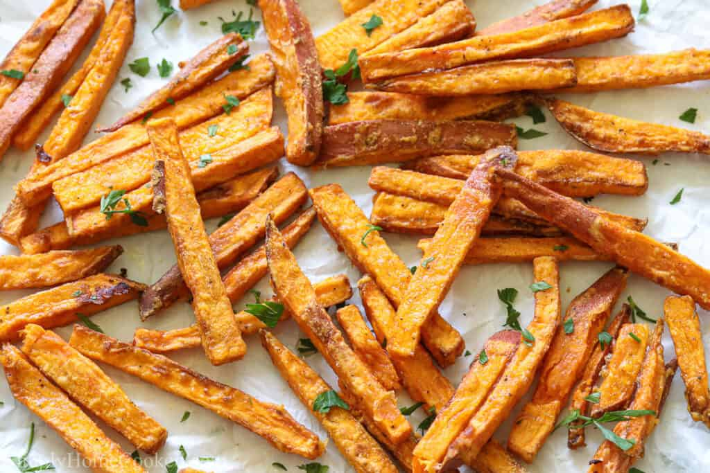 The BEST Air Fryer Sweet Potato Fries on a white background with parsley sprinkled on top.