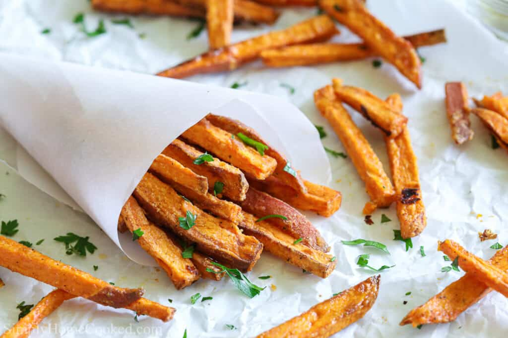 Paper cone of the BEST Air Fryer Sweet Potato Fries, with other fries and parsley scattered on a white paper background.
