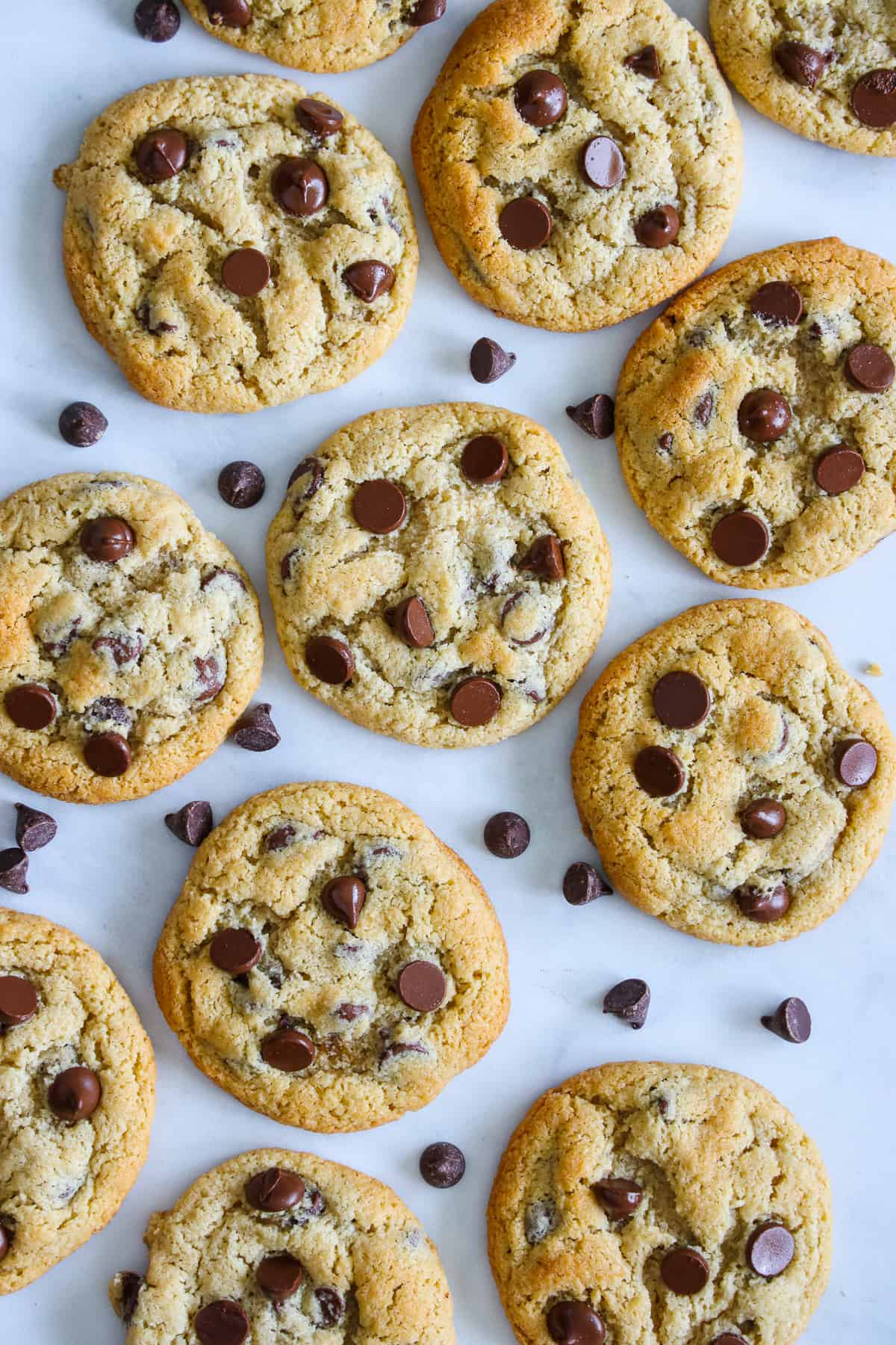 Overhead view of Almond Flour Chocolate Chip Cookies with a scattering of chocolate chips nearby.