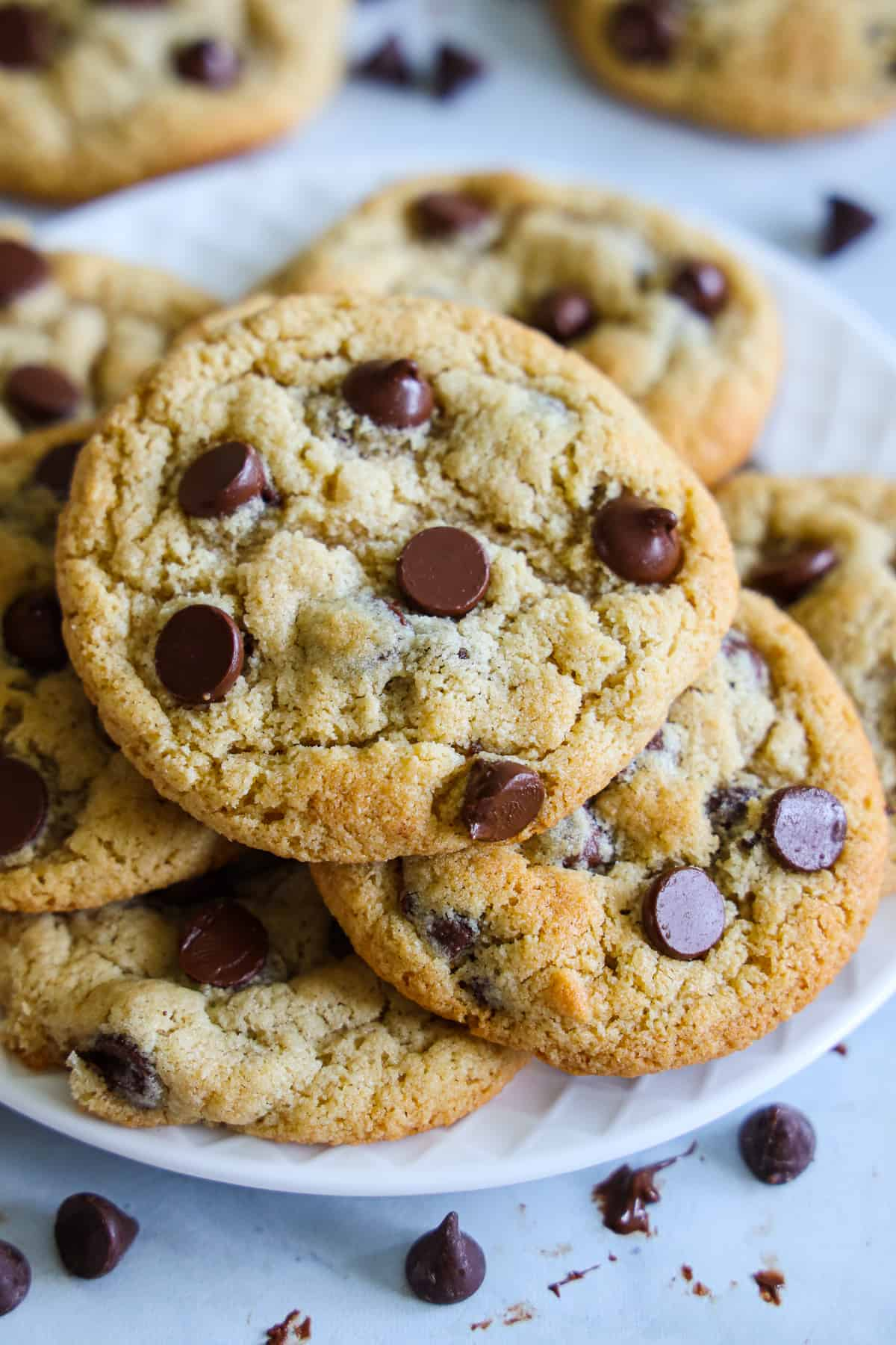 Close up of some Almond Flour Chocolate Chips Cookies on a plate with chocolate chips scattered in the background.