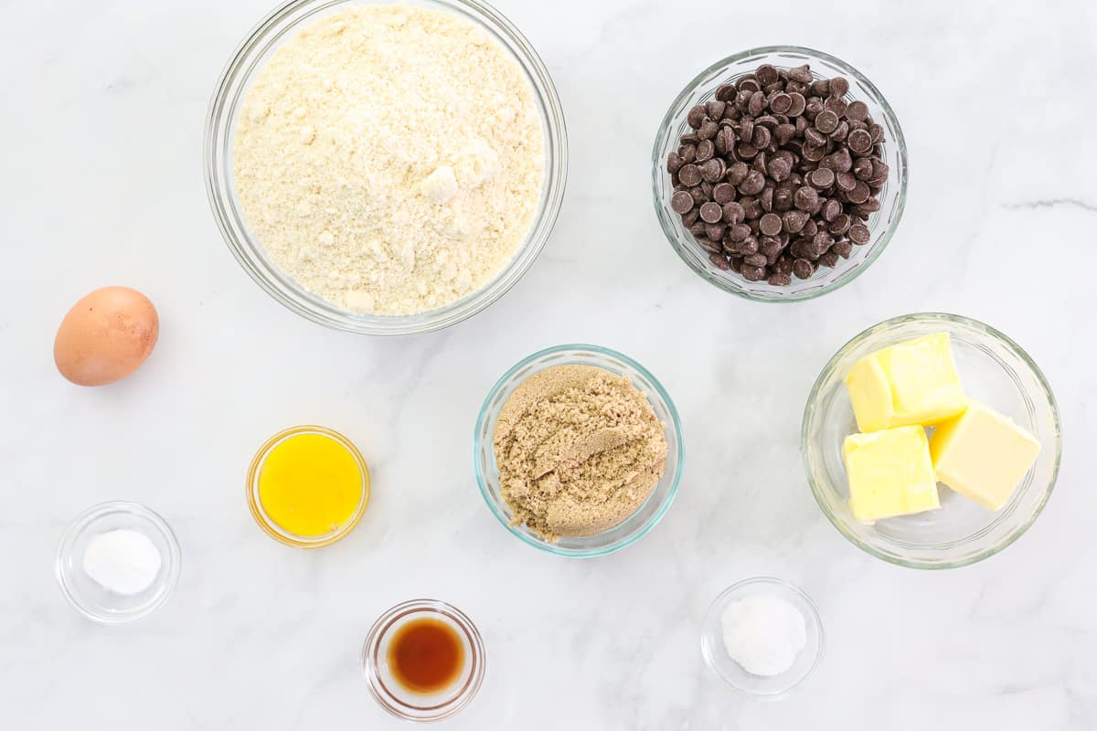 Ingredients for Almond Flour Chocolate Chip Cookies, including blanched almond flour, brown sugar, butter, egg, egg yolk, salt, baking soda, vanilla, and chocolate chips, on a white background.
