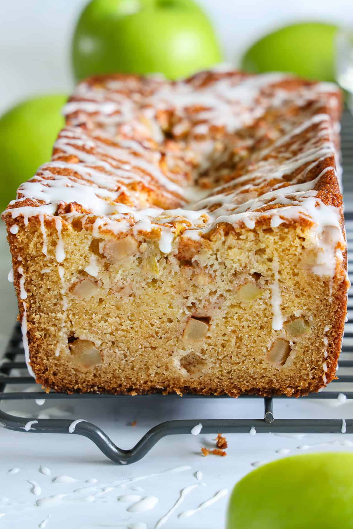 Front view of Apple Fritter Bread covered in glaze with green apples in the background,