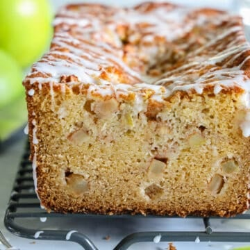 close up image of an apple fritter bread sliced, with white glaze on top and granny smith apples in the background