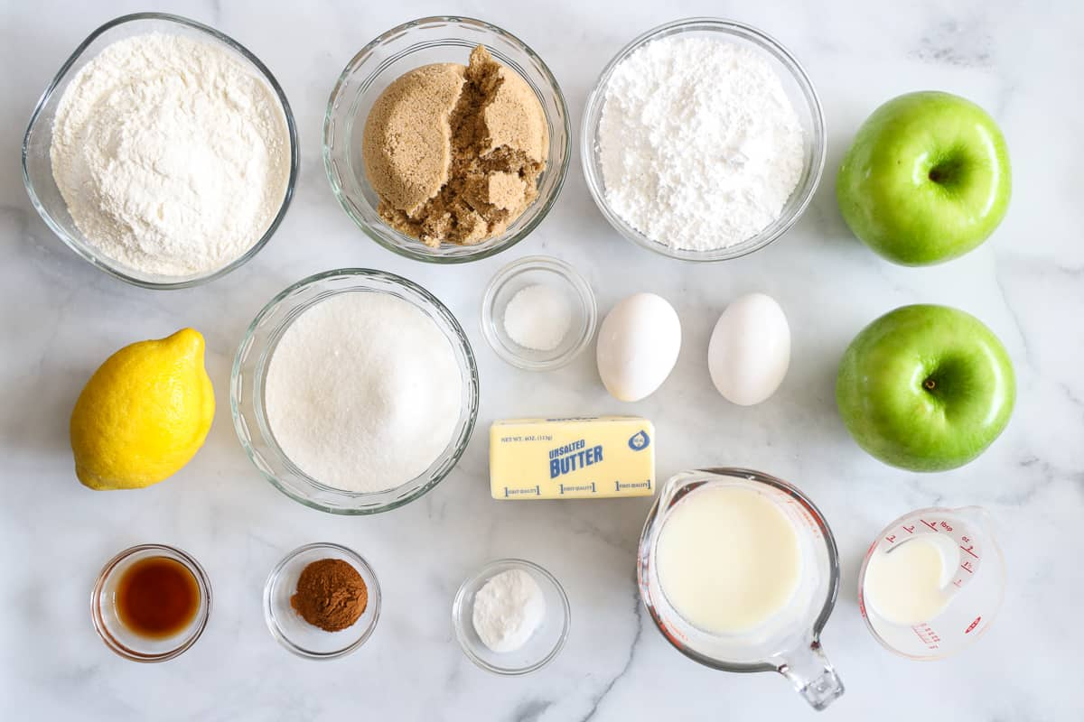Ingredients for Apple Fritter Bread, including flour, sugar, brown sugar, lemon, green apples, eggs, vanilla, cinnamon, salt, butter, buttermilk, and baking soda, milk and powdered sugar for the glaze.