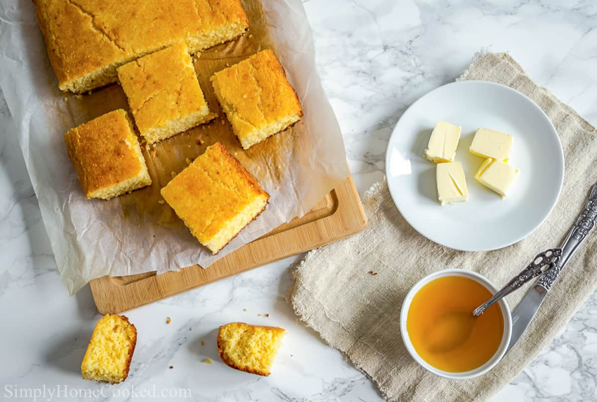 Slices of Moist Buttermilk Cornbread  on a wooden board and a plate of butter with a bowl of honey are to the side with crumbs and a knife.
