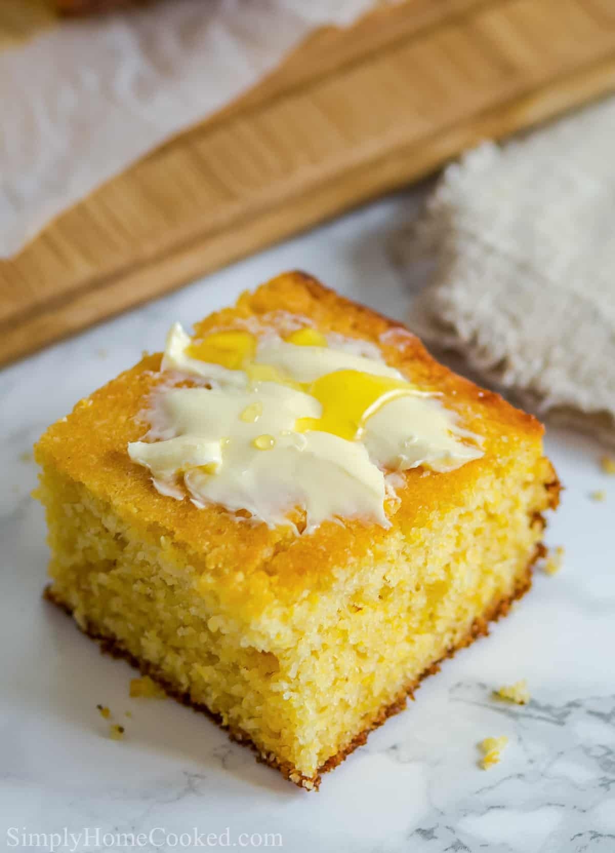 Moist Buttermilk Cornbread slice with butter and honey on top, on a white plate.