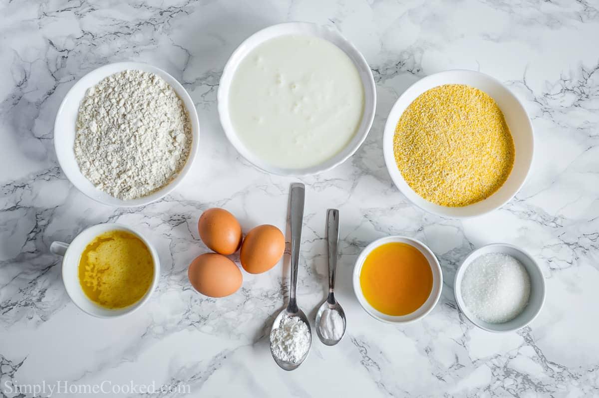 Ingredients for Moist Buttermilk Cornbread, including flour, sugar, eggs, cornmeal, melted butter, salt, honey, baking powder, and baking soda.