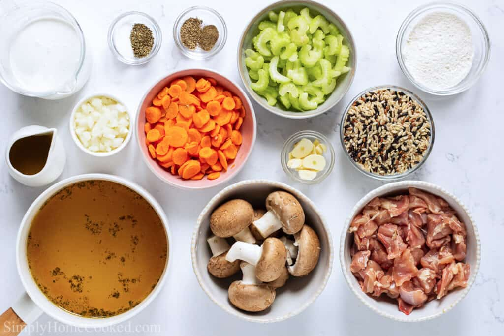 Ingredients for Creamy Chicken and Wild Rice Soup, including chicken thighs, olive oil, chicken broth, heavy cream, flour, celery, carrots, garlic, mushrooms, onion, wild rice, salt, pepper, dried oregano, and thyme.
