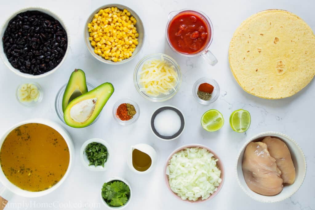 Ingredients for Chicken Tortilla Soup, including corn tortillas, chicken tenders, black beans, frozen corn, diced tomatoes, chicken broth, garlic, onion, shredded cheese, lime, salt, olive oil, cilantro, oregano, cumin, chili powder, and smoked paprika, ona  white background.