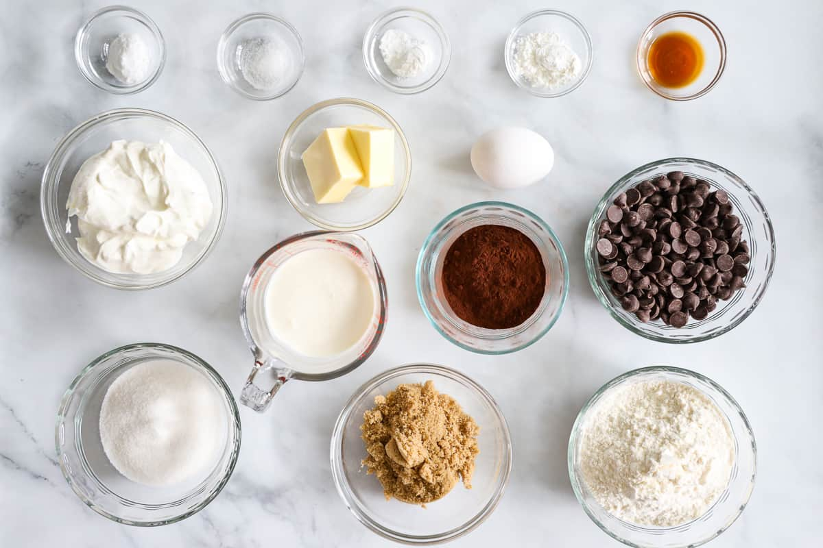 Ingredients for the Best Chocolate Donuts, including butter, sugar, brown sugar, flour, baking soda, baking powder, cornstarch, salt, egg, vanilla, sour cream, heavy cream, and chocolate chips.