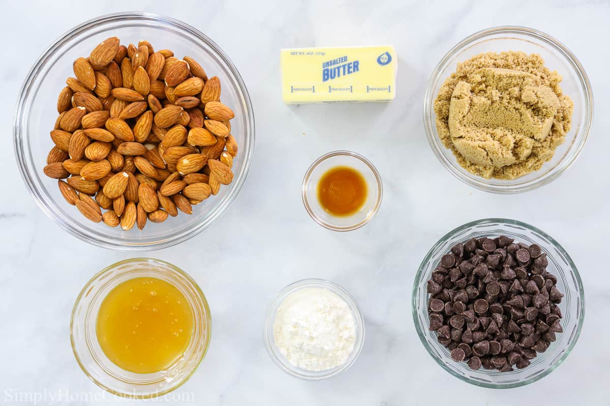 Ingredients for Chocolate Florentine Lace Cookies, including almonds, unsalted butter, golden brown sugar, vanilla extract, honey, all-purpose flour, and semi0sweet chocolate chips on a white background.