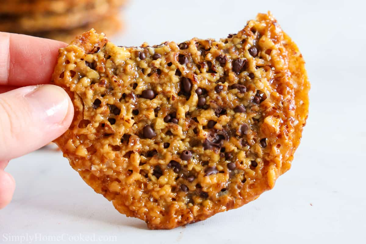 Close up of a hand holding a Chocolate Florentine Lace Cookie with a bite missing, a stack of more cookies in the background.