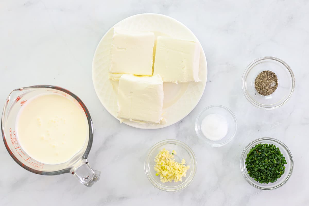 Ingredients for Garlic Cream Cheese Dip, including cream cheese, heavy cream, chives, salt, pepper, and minced garlic, on a white background.