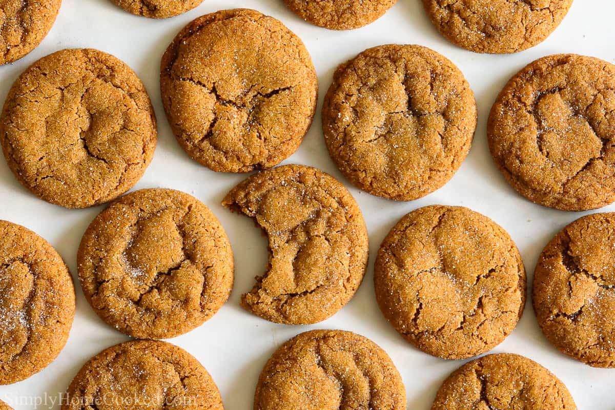 Chewy Ginger Molasses Cookies on parchment paper with one missing a bite.