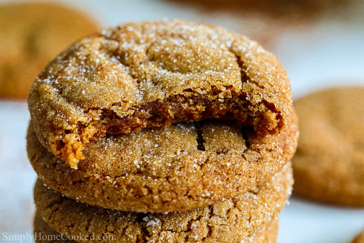 Stack of Chewy Ginger Molasses Cookies with the top one missing a bite, more cookies in the background.