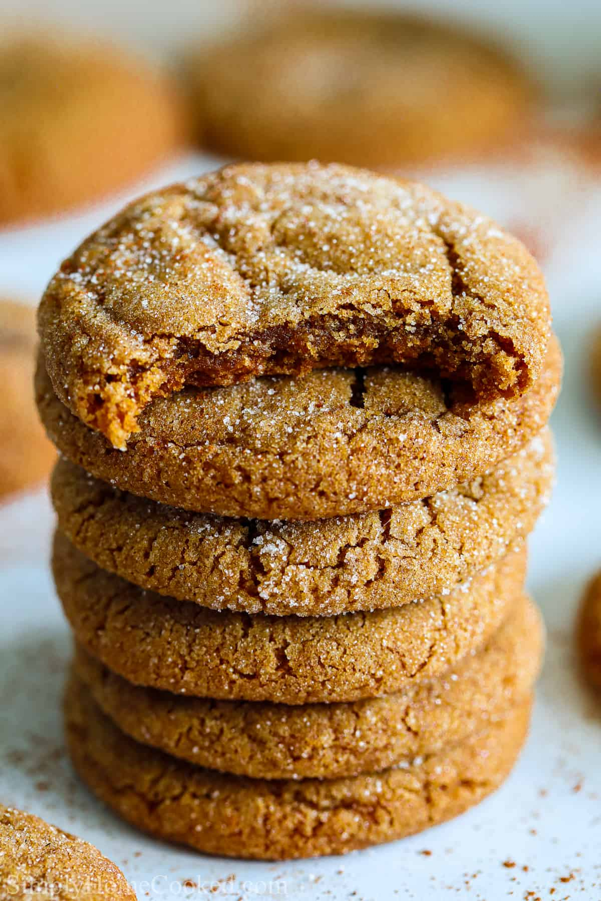 Stack of Chewy Ginger Molasses Cookies, the top one missing a bite.