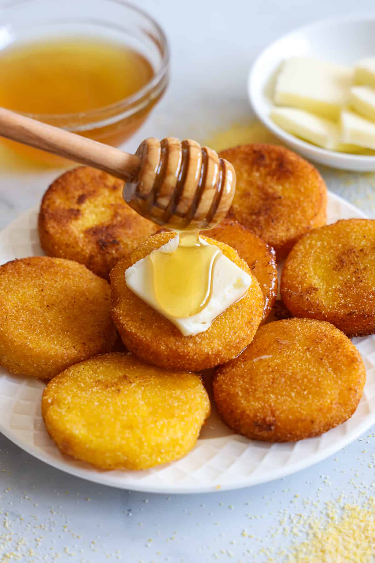 Southern Hot Water Cornbread on a plate with a pat of butter and honey being dribbled on it, honey and butter in the background.