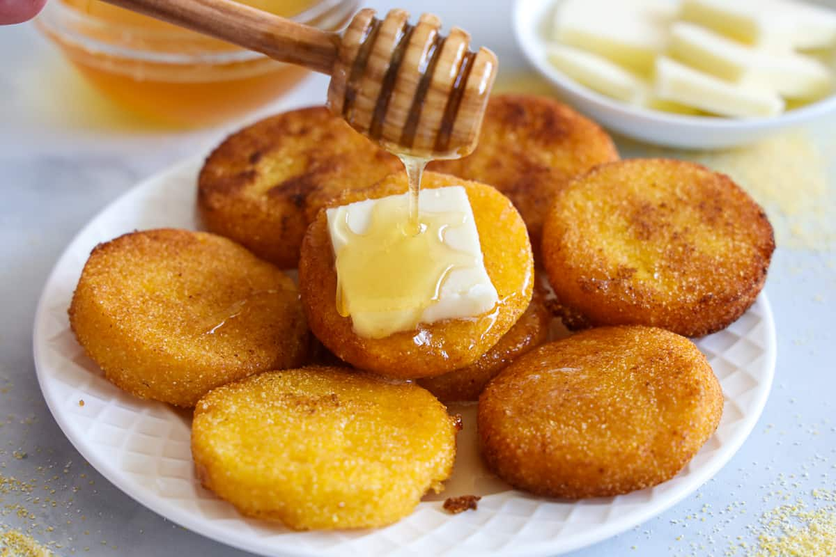 Southern Hot Water Cornbread on a plate with butter and honey being drizzled on it, and more honey and butter in the background.