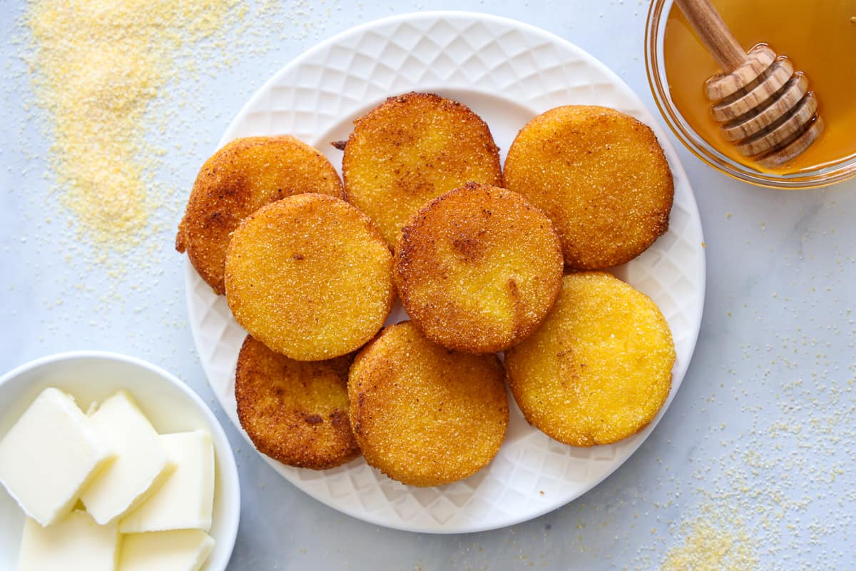 Overhead view of Southern Hot Water Cornbread on a white plate with a bowl of honey and another of butter nearby, some cornmeal scattered to the side.