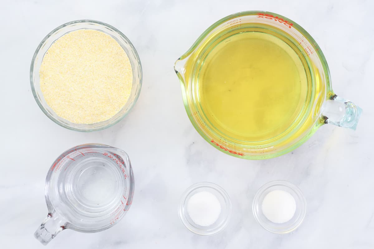 Ingredients for Southern Hot Water Cornbread, including cornmeal, hot water, salt, sugar, and corn oil for frying, on a white background.