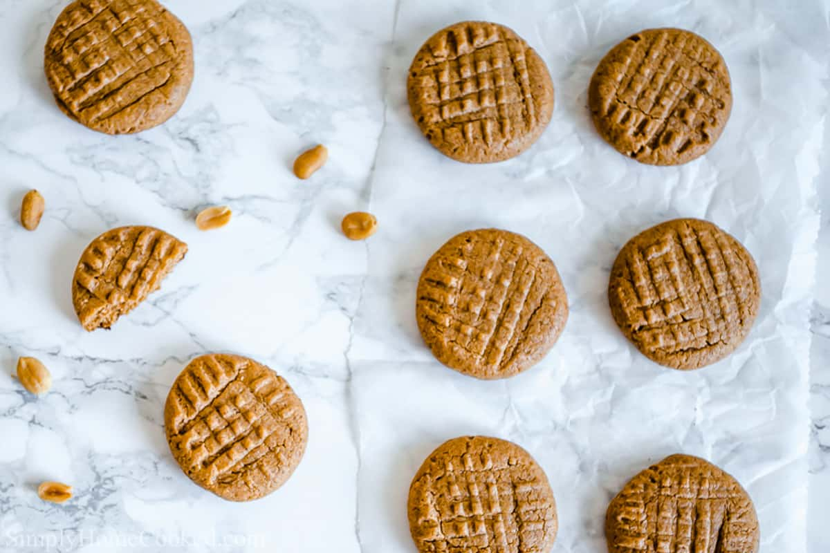 Easy Keto Peanut Butter Cookies on a white background, one broken with some peanuts nearby.