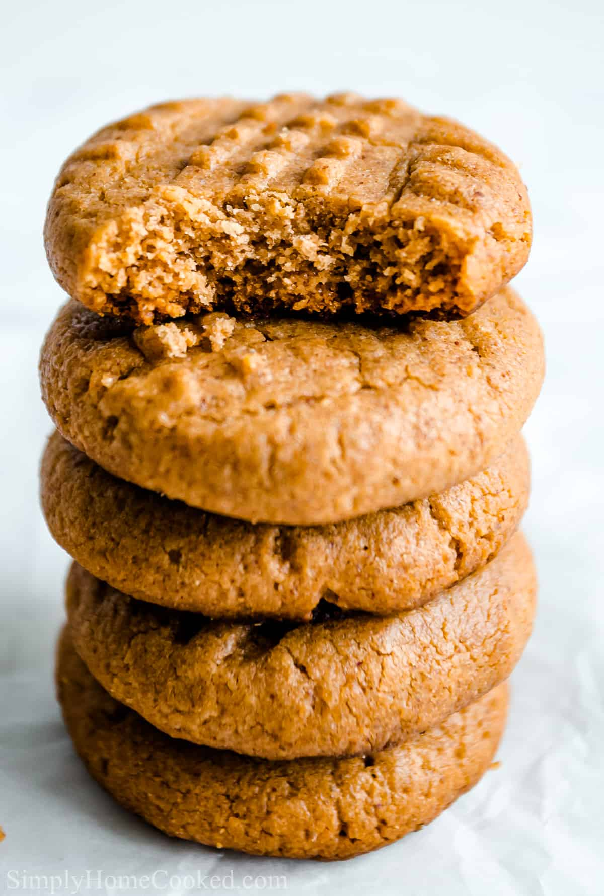 Close up of a stack of Easy Keto Peanut Butter Cookies, the top one missing a bite.