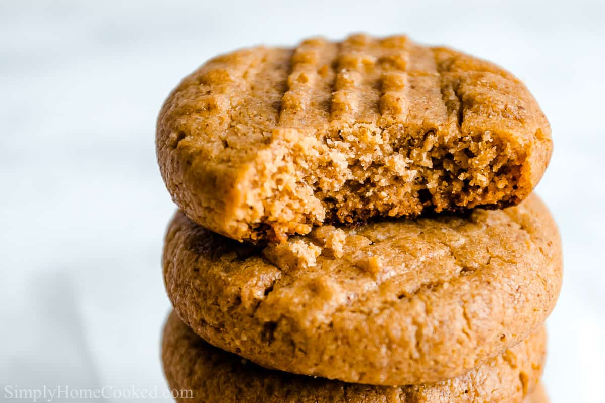 Close up of stack of Easy Keto Peanut Butter Cookies, the top one missing a bite.