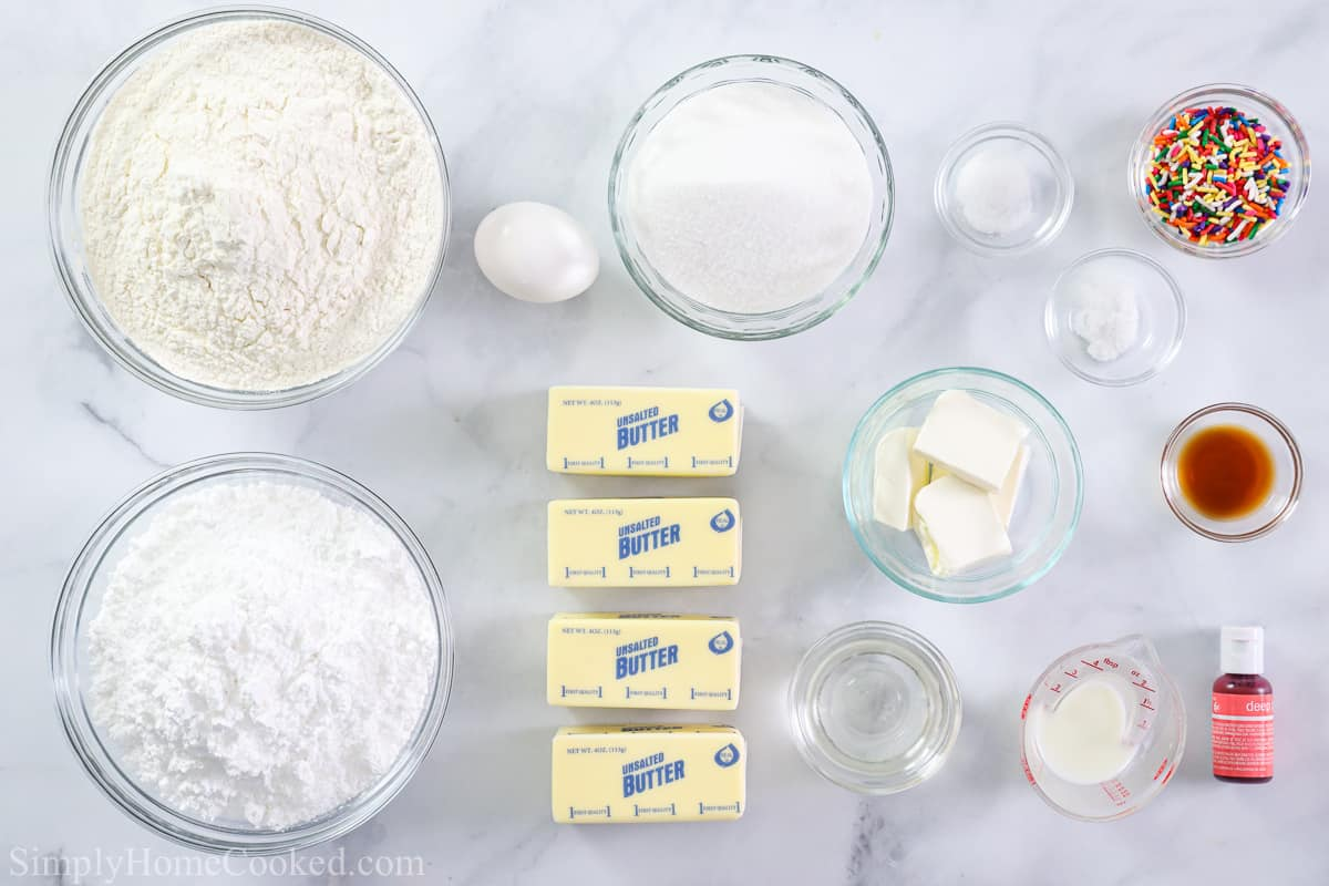 Ingredients for Lofthouse Frosted Sugar Cookies, including butter, flour, sugar, powdered sugar, eggs, baking soda, salt, vanilla, milk, cream cheese, food coloring, and sprinkles, on a white background.
