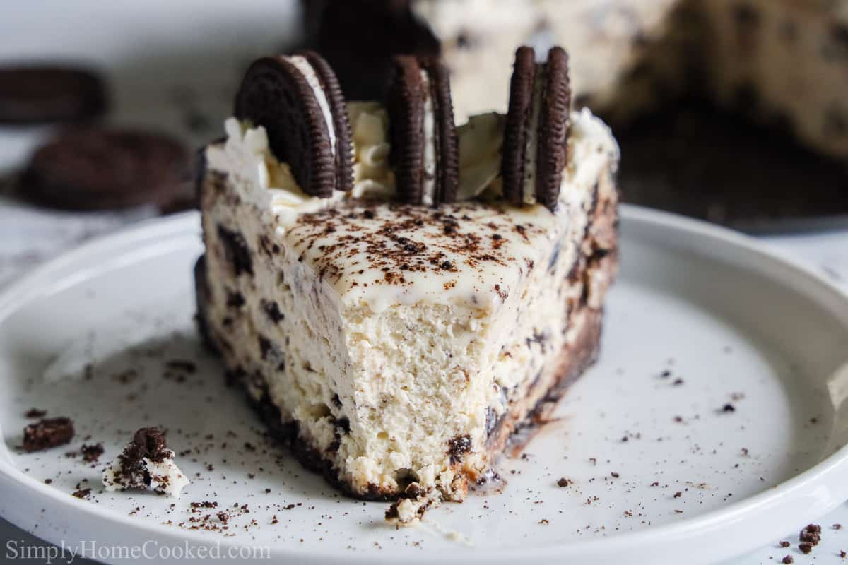 Front view of a slice of Easy Oreo Cheesecake with 3 Oreos on top and crumbs on the white plate.