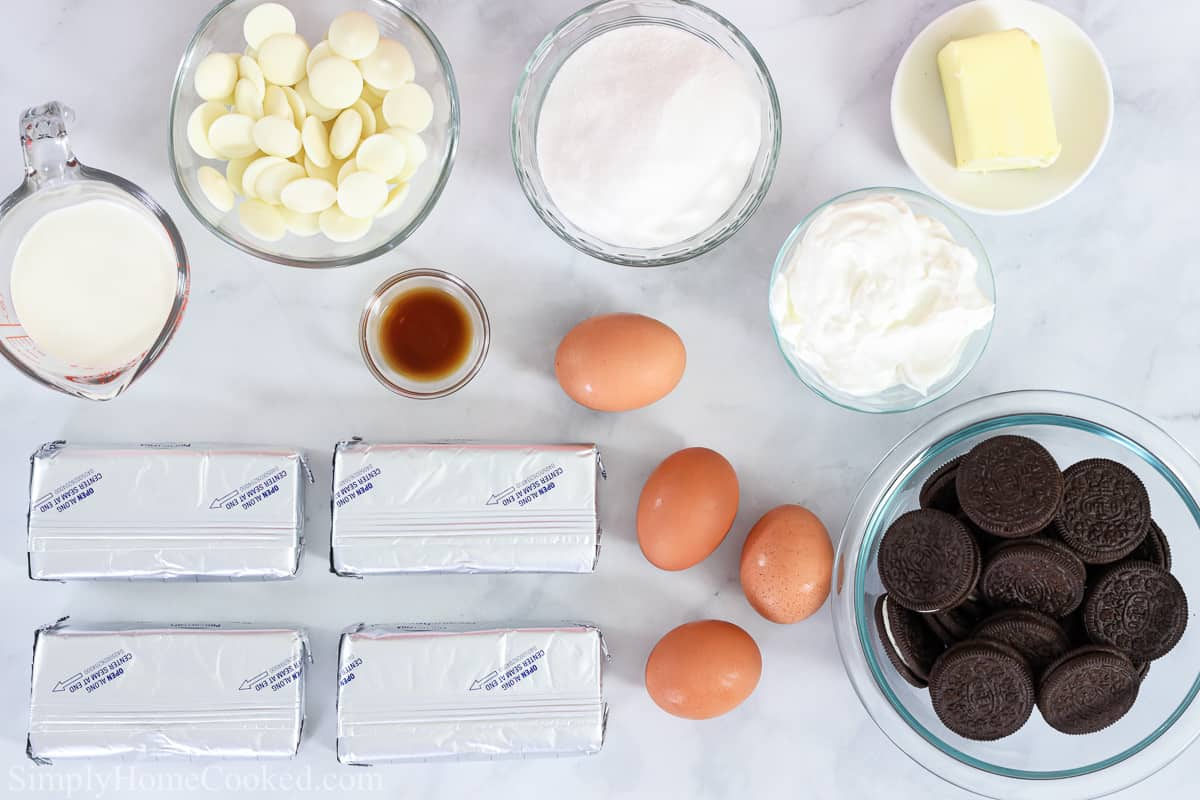 Ingredients for Easy Oreo Cheesecake, including cream cheese, heavy cream, white chocolate melting wafers, sugar, eggs, vanilla, sour cream, butter, and Oreos, on a white background.