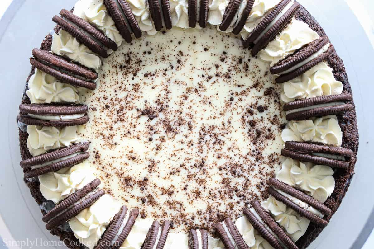 Aerial view of an Easy Oreo Cheesecake, decorated with whipped cream, Oreos, and cookie crumbs.