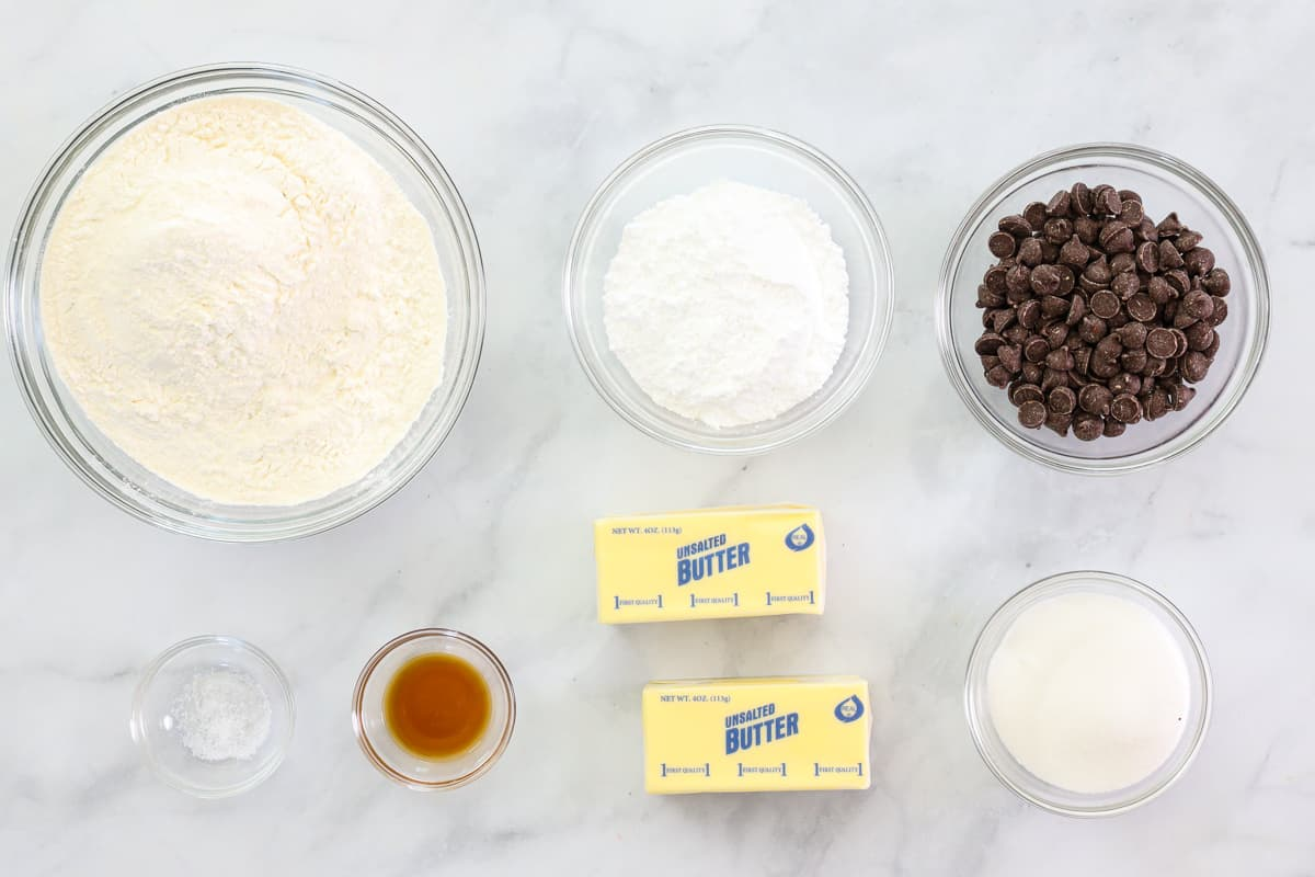 Ingredients for Classic Shortbread Cookies, including flour, butter, salt, sugar, powdered sugar, vanilla, and chocolate chips, on a white background.