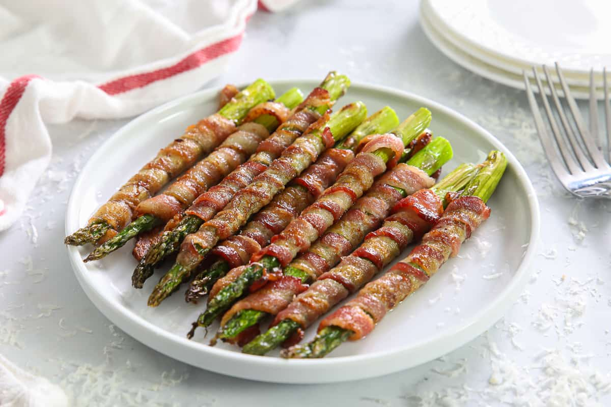 Bacon Wrapped Asparagus on a white plate with more plates, a towel, and a fork nearby.