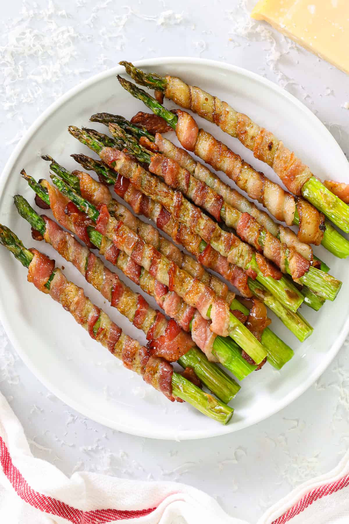 Close up of Bacon Wrapped Asparagus on a white plate.