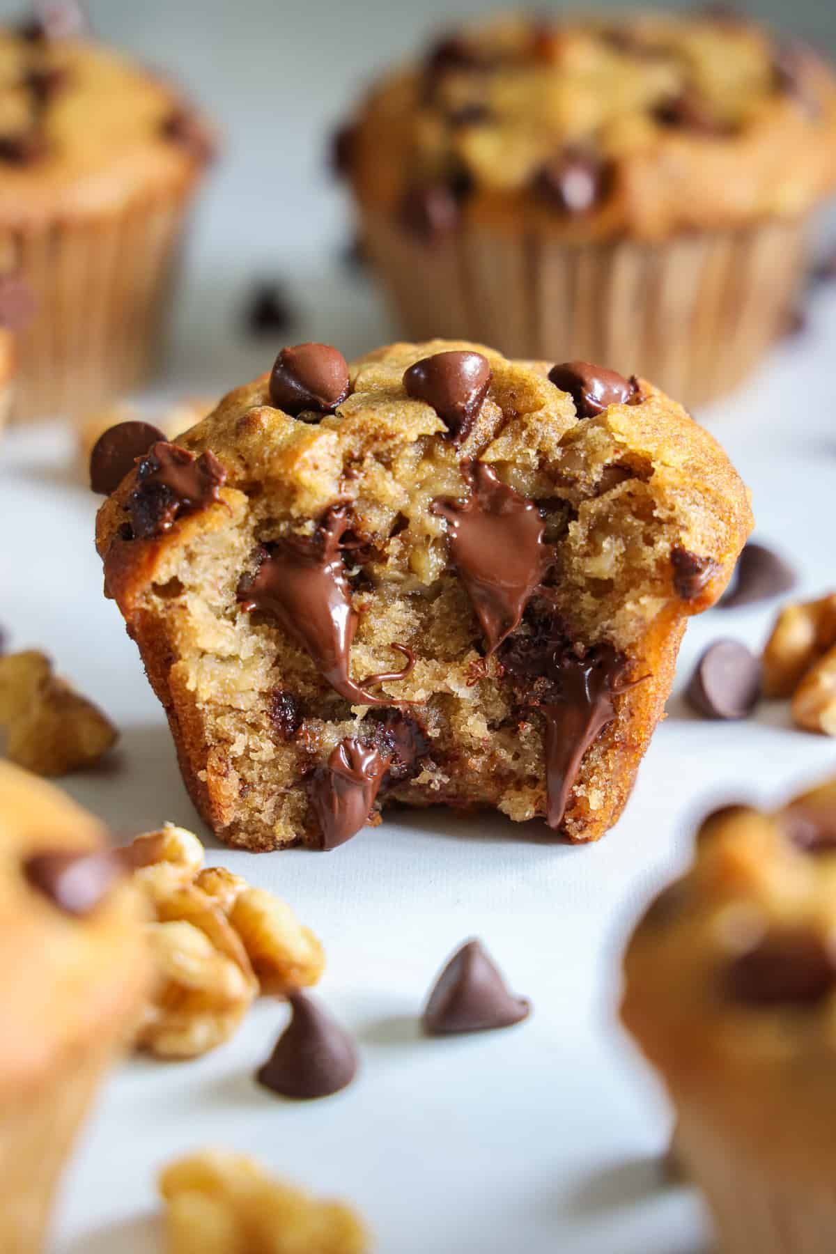 Close up of a Banana Chocolate Chip Muffin missing a bite, with melting chocolate visible, and more muffins in the background.