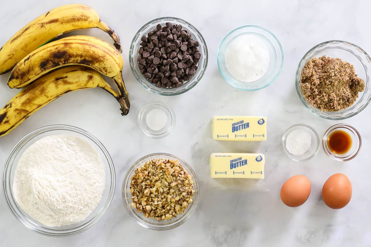 Ingredients for Banana Chocolate Chip Muffins, including bananas, chocolate chips, butter, sugar, brown sugar, eggs, walnuts, flour, salt, baking soda, and vanilla, on a  white background.
