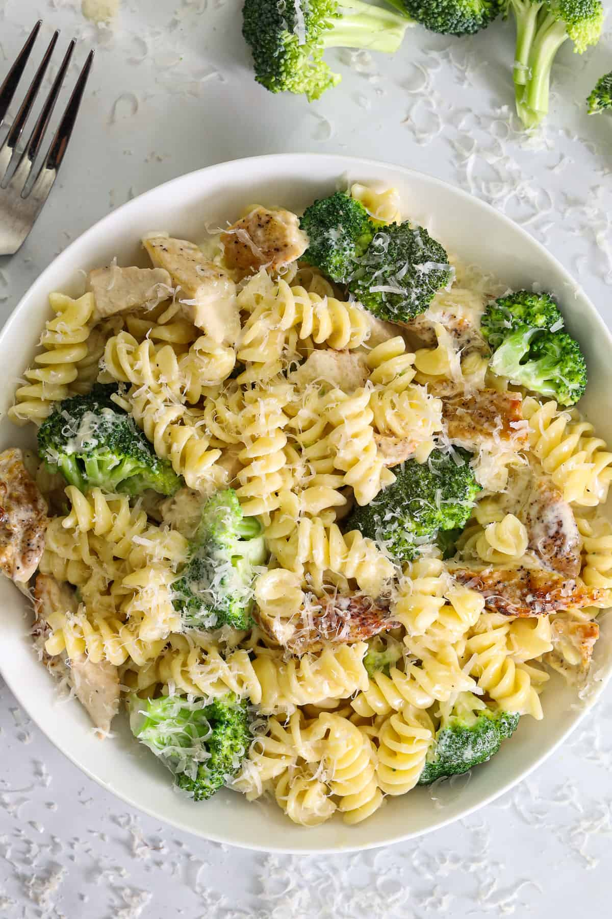 Close up of Chicken Broccoli Alfredo in a white bowl with Parmesan cheese on top and a fork and broccoli nearby.