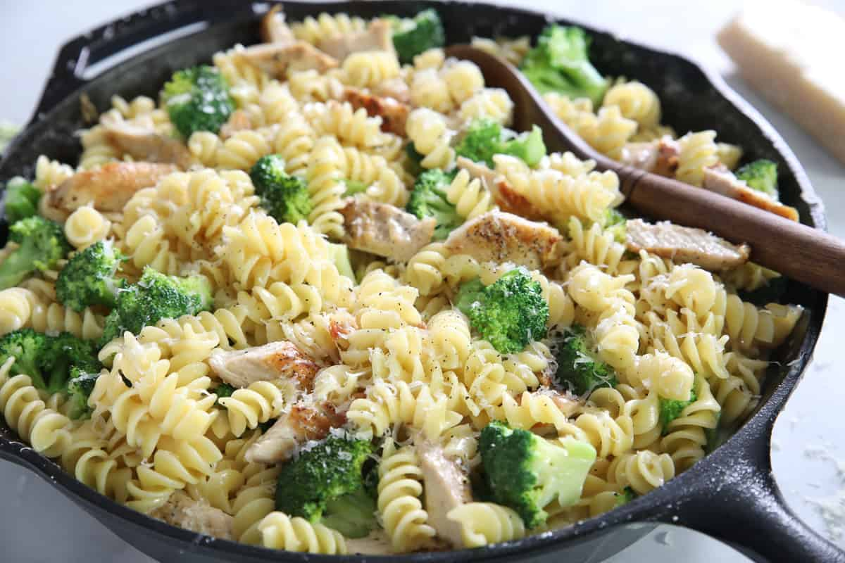Chicken Broccoli Alfredo in a skillet with a wooden spoon laying in it.
