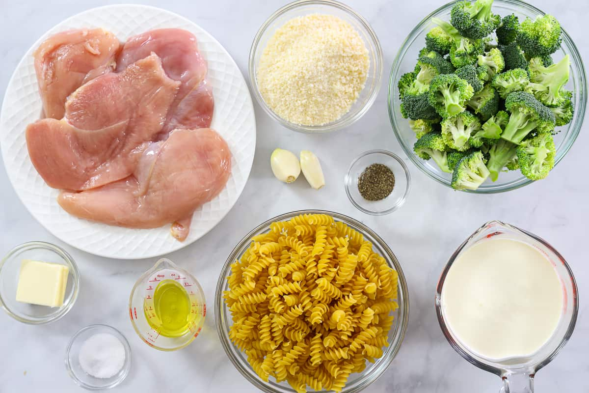Ingredients for Chicken Broccoli Alfredo, including chicken breast cutlets, Parmesan cheese, broccoli florets, garlic cloves, salt, pepper, olive oil, butter, rotini pasta, and heavy cream, on a white background.