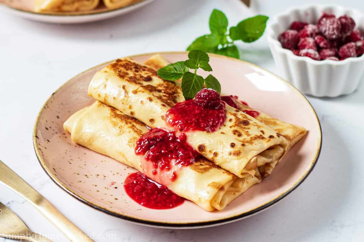 Cheese Blintz on a plate with berry sauce and garnished on top, with silverware nearby and a bowl of raspberries in the background.