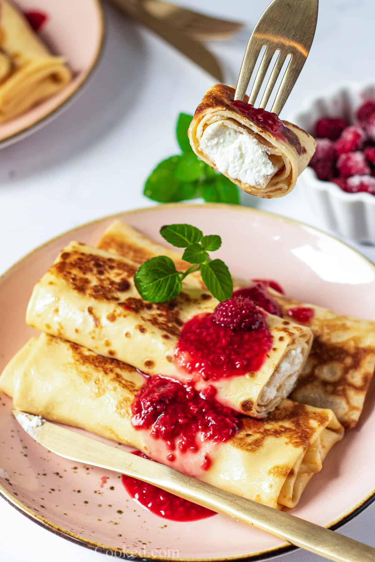 Closeup of a Cheese Blintz with berry sauce and a garnish on top, a knife next to them on the plate and a fork with a piece of blintz on it.