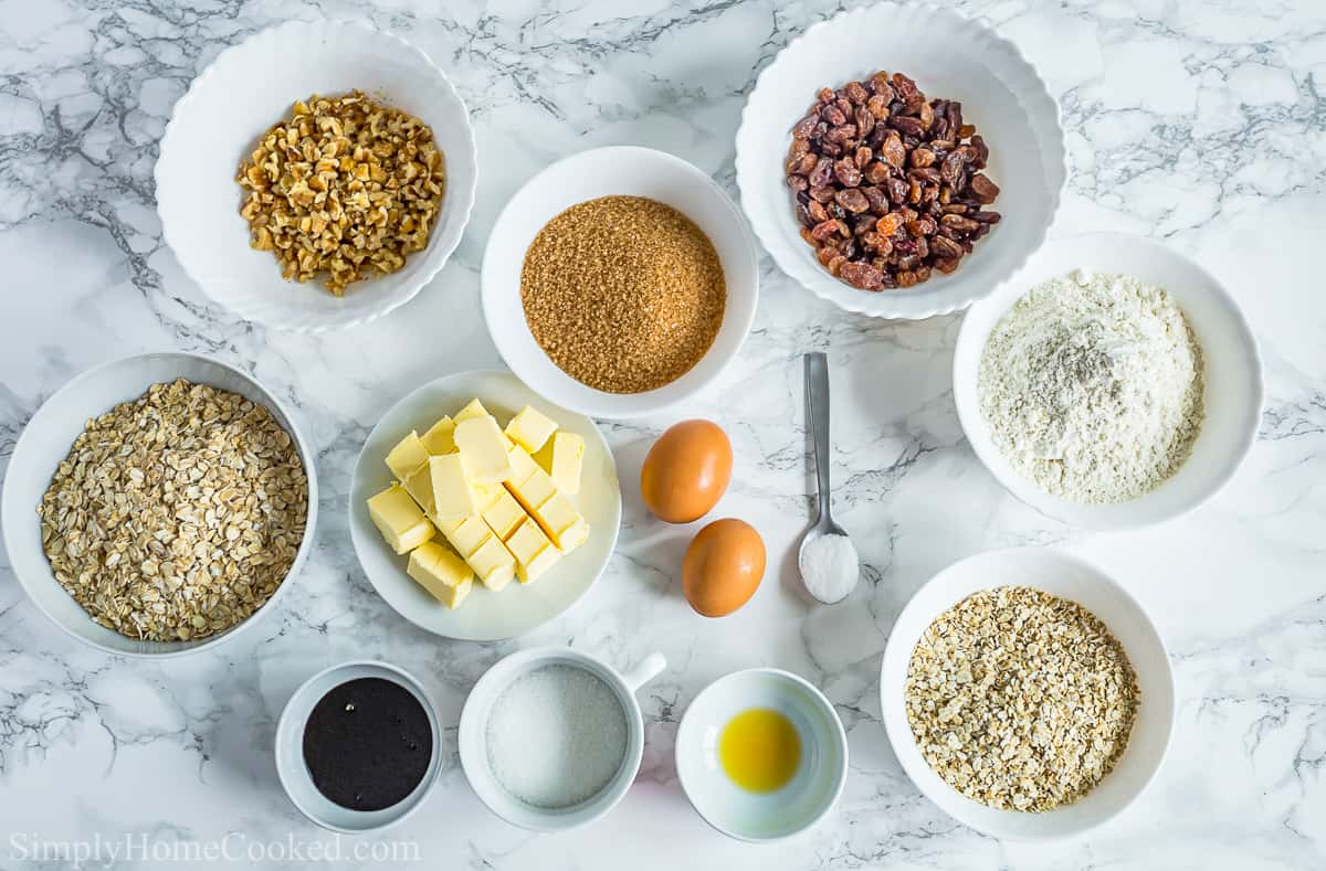 Ingredients for Oatmeal Raisin Cookies, including flour, quick oats, old-fashioned oats, butter, raising, walnuts, eggs, sugar, brown sugar, molasses, baking soda, and salt, on a white background.