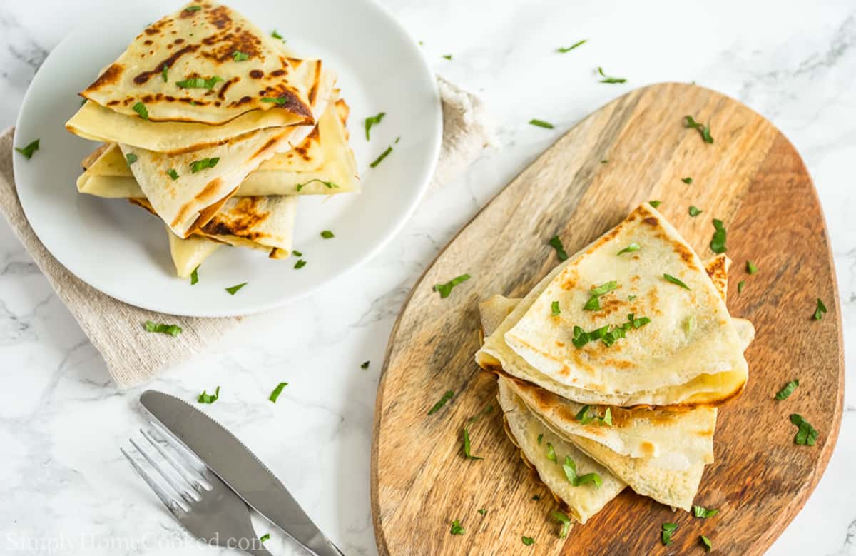 Savory Crepes with Chicken and Mushroom Filling stacked on a wooden board and more on a white plate, with garnish sprinkled on top and a fork and knife nearby.