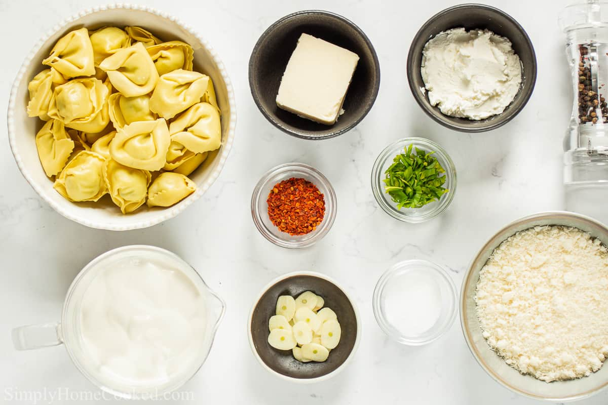 Ingredients for Creamy Tortellini Alfredo, including cheese tortellini, heavy cream, cream cheese, butter, garlic, Parmesan, salt, pepper, red pepper flakes, and parsley on a white background.