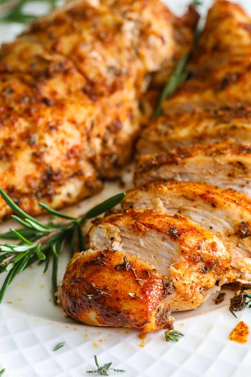 Close up of Juicy Air Fryer Chicken Breast sliced and garnished with rosemary.