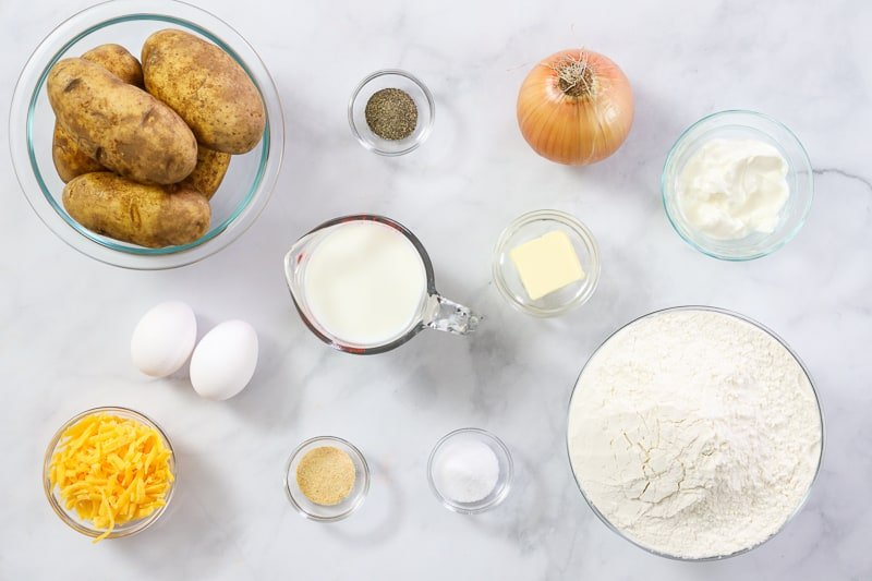 Ingredients for Potato Pierogi, including potatoes, onion, eggs, cheddar cheese, flour, sour cream, milk, garlic powder, salt, and pepper, on a white background.
