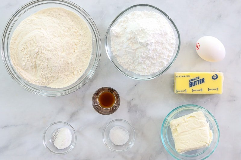 Ingredients for Easy Cream Cheese Cookies, including flour, powdered sugar, butter, cream cheese, vanilla extract, egg, baking powder, and salt, on a white background.